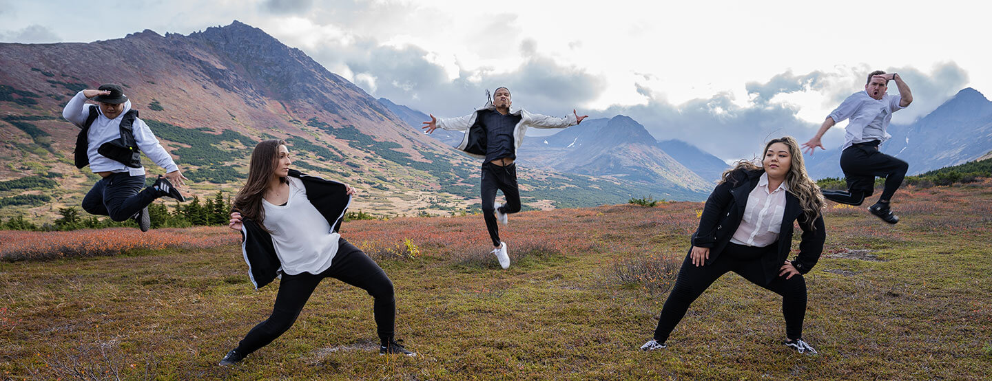 Multiple dancers on top of beautiful Alaskan mountains.